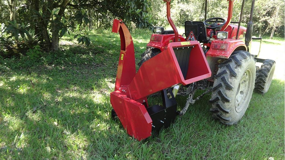 Tractor-driven shredder for shrubs, branches and logs.