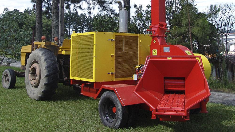 Picador florestal com acionamento a partir de motor próprio a diesel, capaz de picar toras com até 260 mm de diâmetro e produção de até 55m³/h.