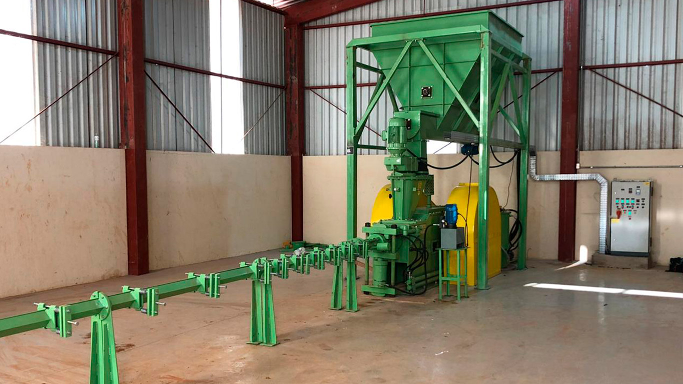 Briquette machine with temporary storage for feeding