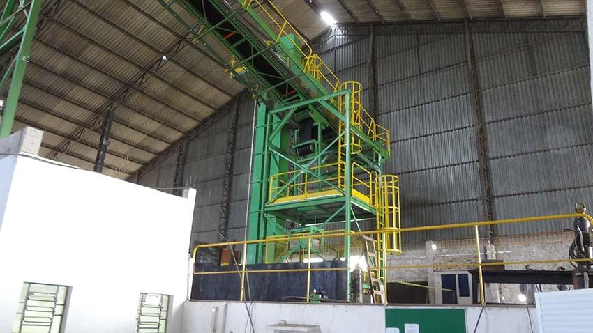 Descarregamento vertical da biomassa do elevador de canecos sobre correia transportadora.
